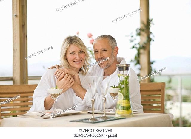 Couple in bathrobes having breakfast
