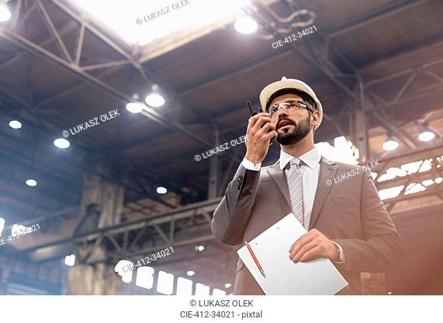 Manager with walkie-talkie in steel factory
