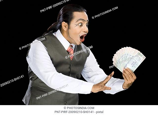 Close-up of a mime holding currency notes