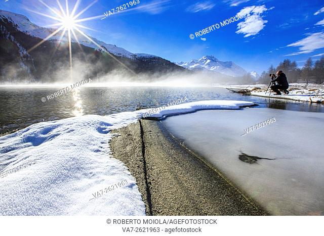 Photographer in action on the icy shores of Lake Silvaplana Saint Moritz Maloja Engadine Graubunden Canton Switzerland Europe