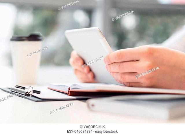 In pace with time. Selective focus of tablet in hands of pleasant man holding it while sitting at the table
