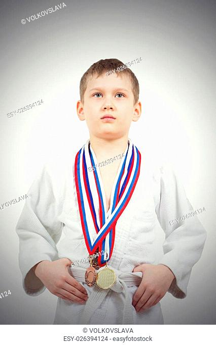 Karate boy in white kimono with medals fighting isolated on white background