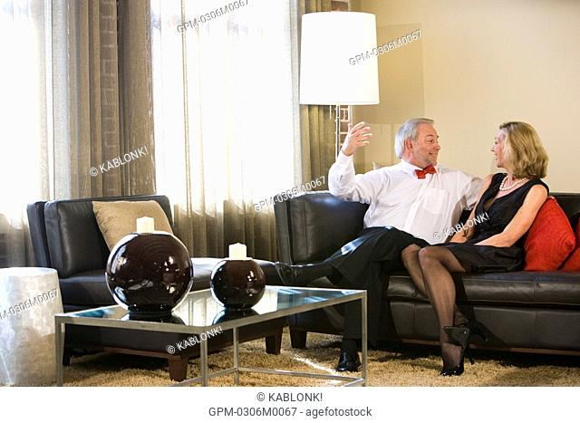Mature couple talking on couch in modern downtown loft