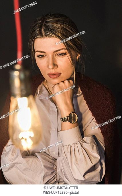 Young woman looking at illuminated light bulb