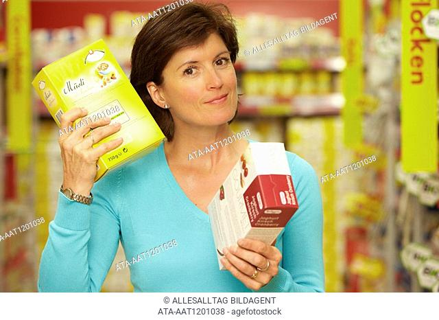 Woman shaking a package in the supermarket