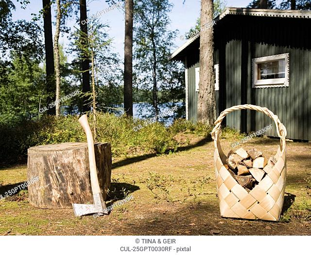 Axe and firewood by wooden cabin