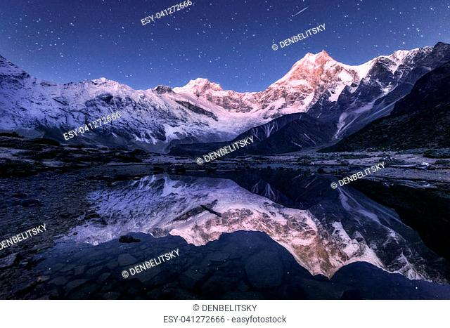 Amazing night scene with himalayan mountains and mountain lake at starry night in Nepal. Landscape with high rocks with snowy peak and sky with stars reflected...