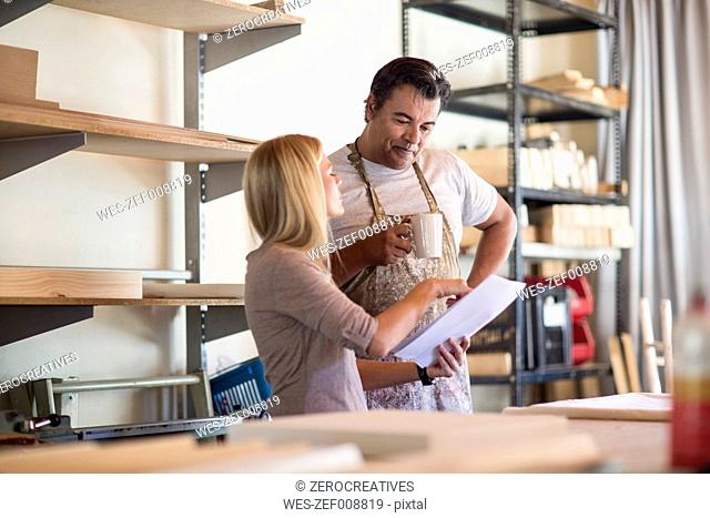 Man and woman discussing plans in canvas workshop