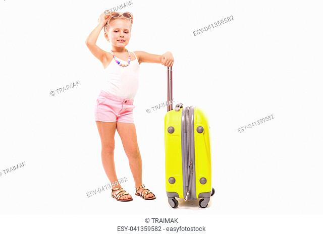 Isolated on white, attractive young caucasian blonde girl in white shirt, pink shorts, sunglasses and sandals stand near the yellow suicase, hand on head