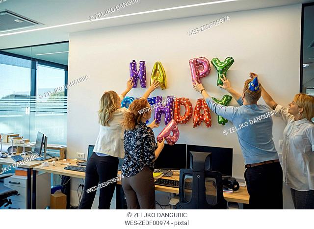 Colleagues decorating office with happy birthday writing