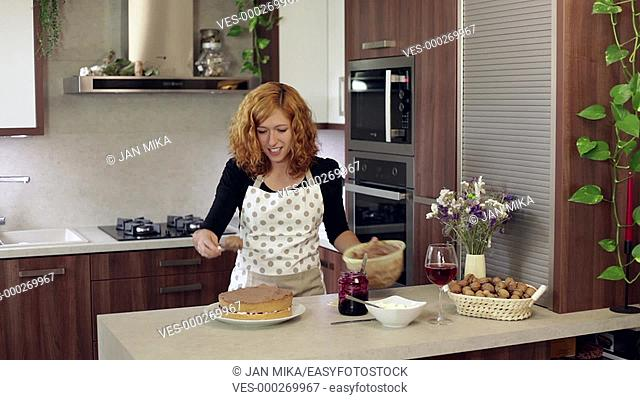 Young happy woman putting chocolate cream on homemade cake in the kitchen at home