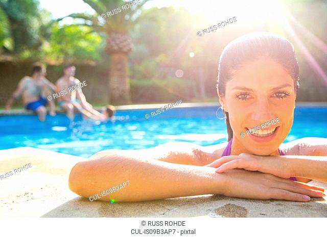 Woman in swimming pool resting on poolside looking at camera smiling