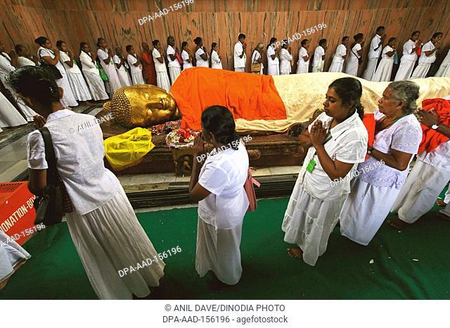 Devotees offering pray ; statue of Lord Buddha's nirwan Mahaparinirvan ; Buddhist site ; Kushinagar ; Uttar Pradesh ; India