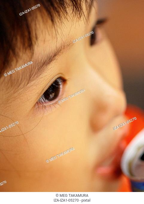 Close-up of a girl drinking canned juice