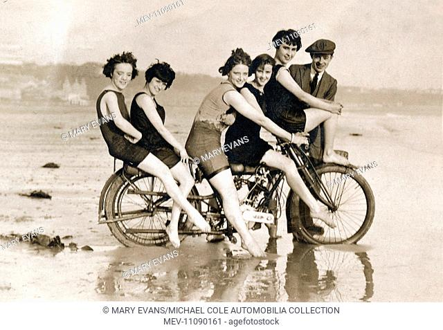 Five young ladies in swimming costumes pose for a photograph,(with a young man), sitting on a circa 1912 B.A.T. 500cc JAP engined motorcycle on the beach at the...