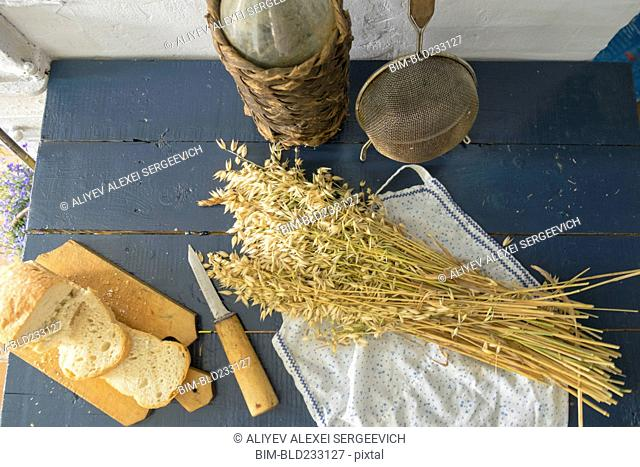 Wheat, sliced bread, sieve and bottle on bench