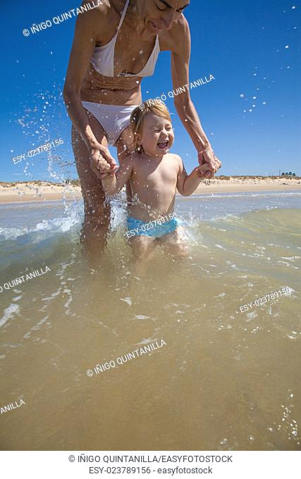 summer happy family of two years blonde baby with blue swimsuit playing and jumping water waves holding hand with woman mother bikini in sea shore beach sand in...