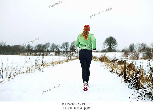 Female jogger running in snow