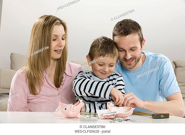 Parents and son 4-5 looking at broken piggybank, counting money