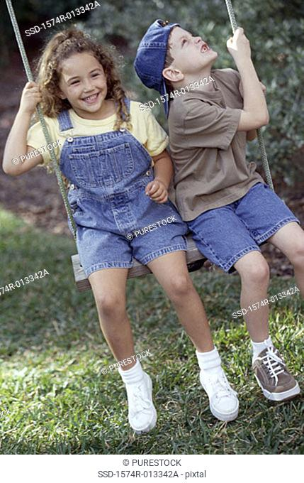 Boy and girl swinging on a rope swing