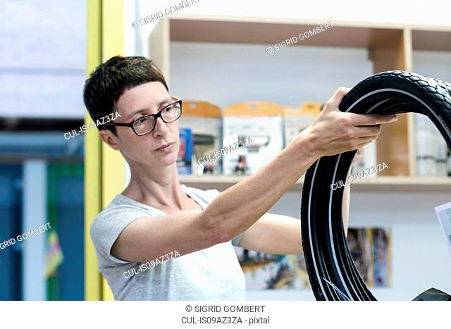 Woman in workshop checking bicycle tyres
