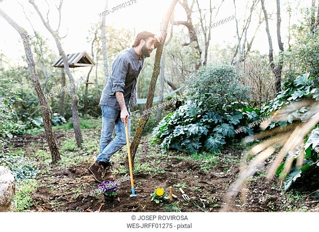 Man in garden having a break from gardening