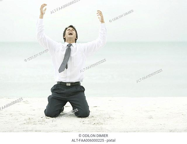 Businessman on beach, on knees with arms in air and head back