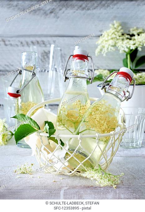 Elderflower syrup in small bottles in a wire basket