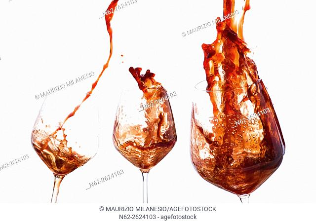 Three glasses of wine overflowing wine splashing up on a white background