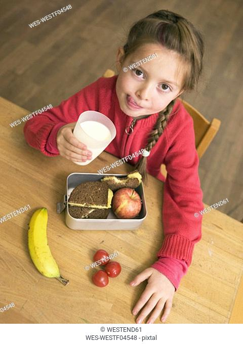 Girl with lunch box on desk, holding glass of milk