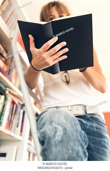 Woman reading a book at bookshelf