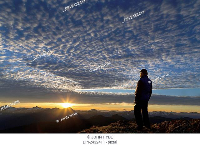View of Coast Mountains and hiker at sunrise in the alpine on Douglas Island in Alaska's Tongass National Forest, Juneau. Alaska