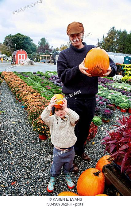 Portrait of boy and his father holding pumpkins at garden centre