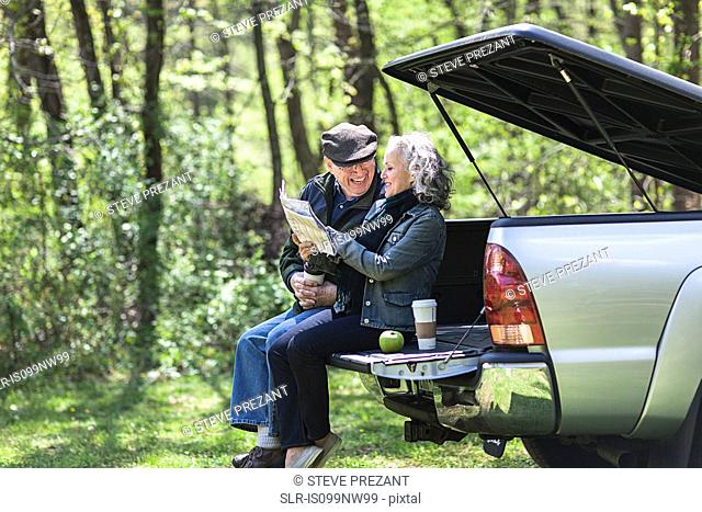 Senior couple reading map while sitting on car trunk in forest