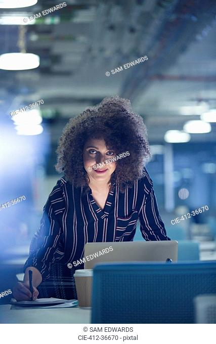 Portrait smiling confident businesswoman working late at laptop in dark office