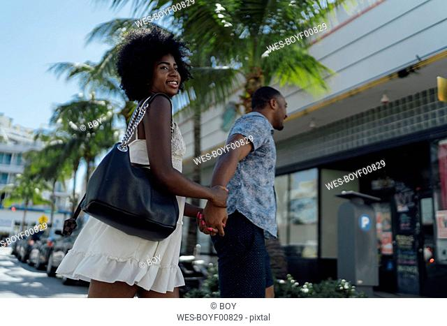 USA, Florida, Miami Beach, happy young couple crossing the street