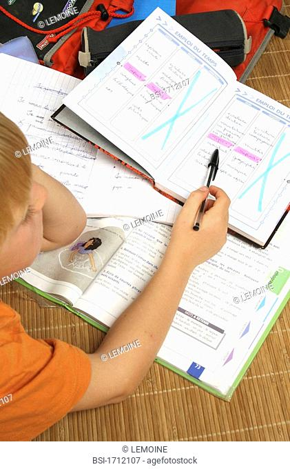 CHILD DOING HOMEWORK Model. 6-and-half-year-old boy, looking at his timetable of the week. Illustration of the school rhythm