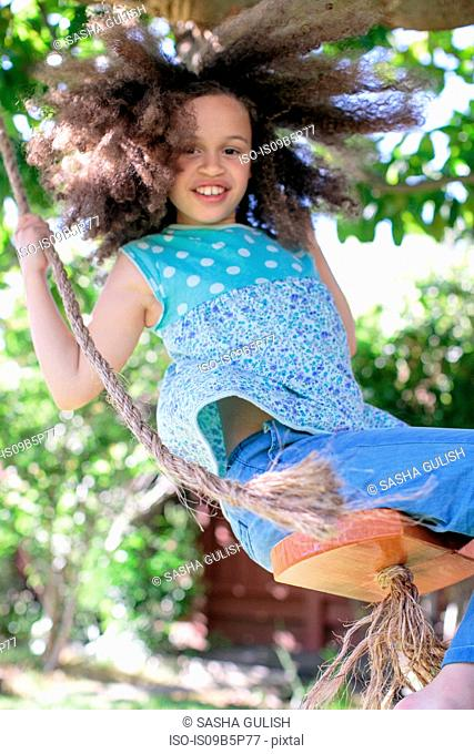 Portrait of young girl on rope swing
