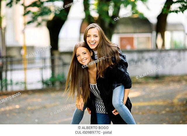Portrait of young woman giving best friend a piggy back in park