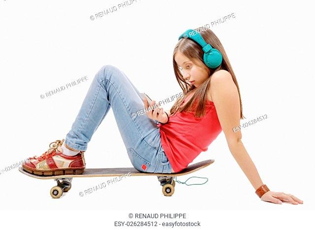 a pretty young girl posing with a skateboard, sitting on skate, listen a music