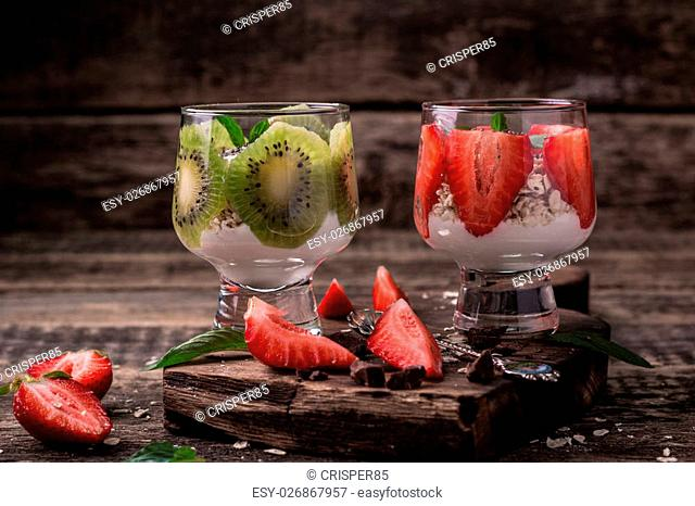 Healthy breakfast or morning snack with chia seeds granola, strawberries and kiwi, vegetarian food, diet and health concept