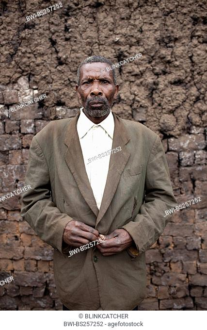 older man in a shirt and jacket standing in front of a traditional furnace in which mud bricks are burned, Burundi, Kabezi
