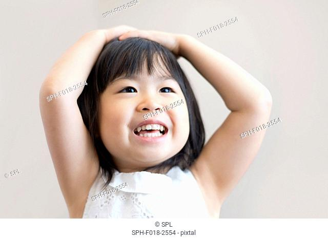 Young girl with hands on head smiling, studio shot