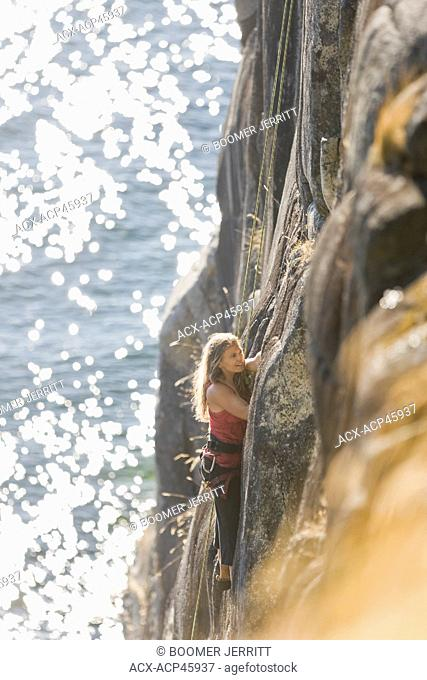 A female climber makes her way up one of the oceanside routes at Stillwater Bluffs south of Powell River on the Sunshine Coast, British Columbia, Canada