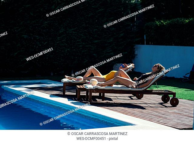 Two beautiful women sunbathing on a terrace next to the pool