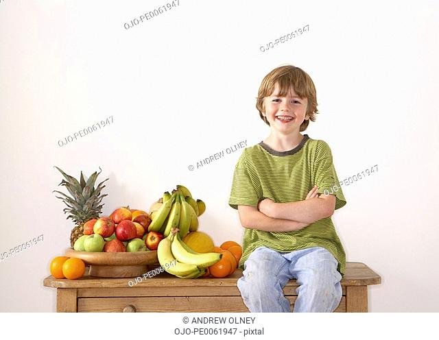 Young boy sitting on kitchen island with assorted fruit smiling