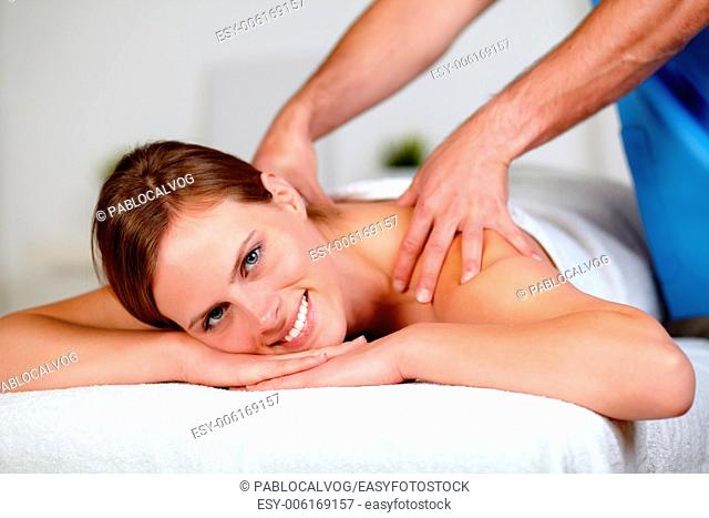 Close up portrait of a beautiful young woman getting a professional massage at spa resort