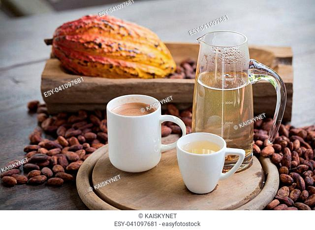 Hot cocoa and milk, Ripe cocoa pod and beans setup on rustic wooden background