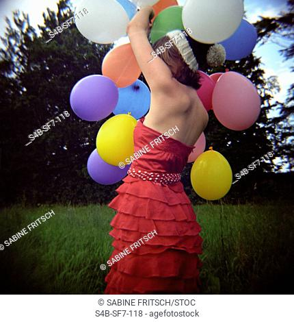 Teenage girl holding balloons in meadow, Bavaria, Germany