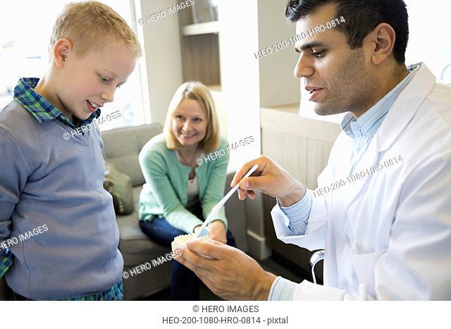 Dentist showing boy how to brush teeth